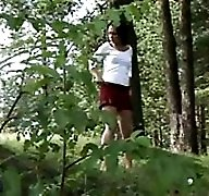 Cute brunette takes a leak on the slope of a hill