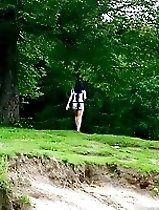Kinky brunette pissing off a cliff in the woods